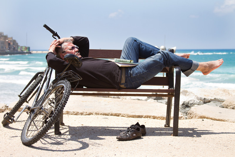 A man takes a quick nap near the coastal shore of Tel Aviv, Israel.