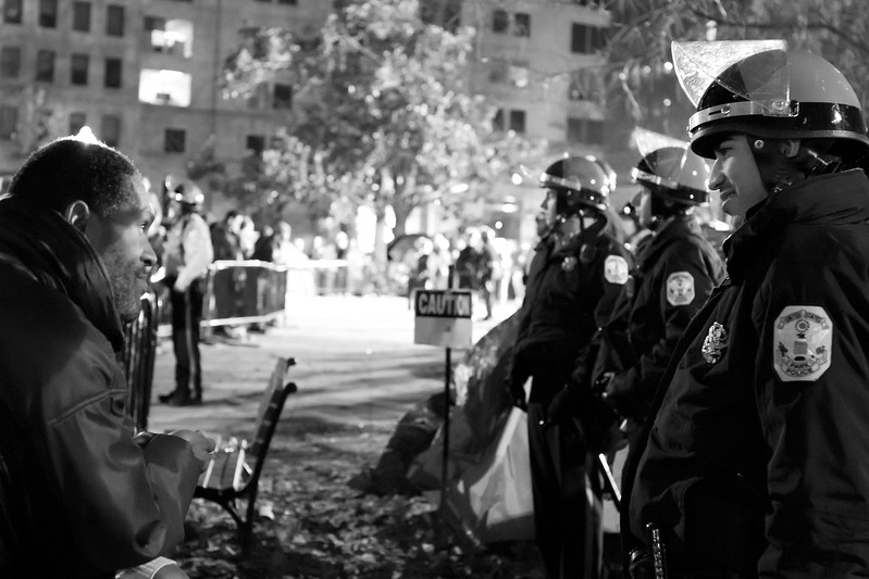 A protester and a Washington, D.C. police officer find common ground after an argument at an Occupy D.C. gathering.  Police were removing a large wooden structure that had been erected by the members of the Occupy movement.